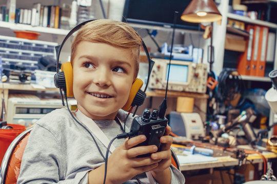Smiling boy with headphones using walkie talkie.