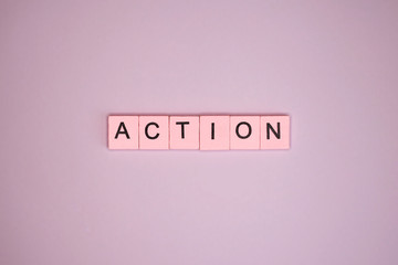 Action word wooden cubes on a pink background