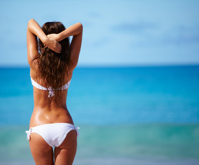 Young woman standing on beach and enjoying sun