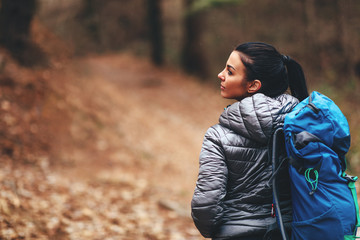 Young woman with blue backpack hiking through forest