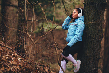 Young woman in a blue jacket in the woods resting leaning on a tree and listening to music via headphones