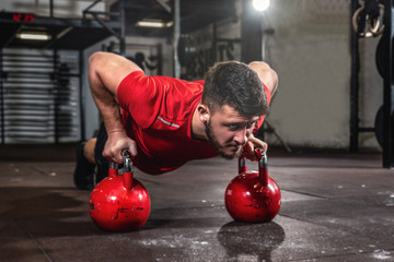 Young fit sweaty muscular man with big muscles doing push ups on two big old heavy kettlebells with his hands for hard core cross workout training on the gym floor
