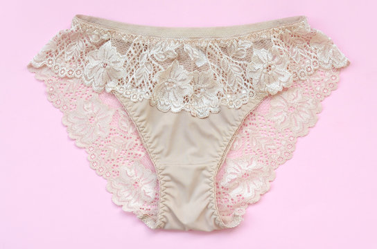 Beige women underwear with lace on pink background with copy space. Beauty fashion blogger concept. Romantic lingerie for Valentines day temptation