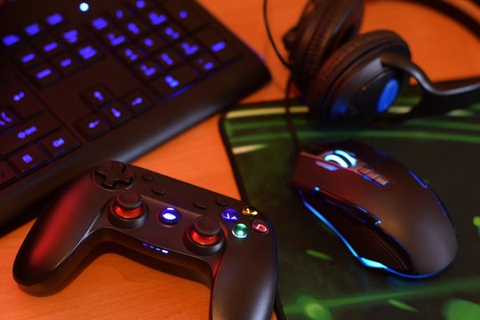 Modern gamepad and gaming mouse lies with keyboard and headphones on table in dark playroom scene. Lets play video games together with friends concept