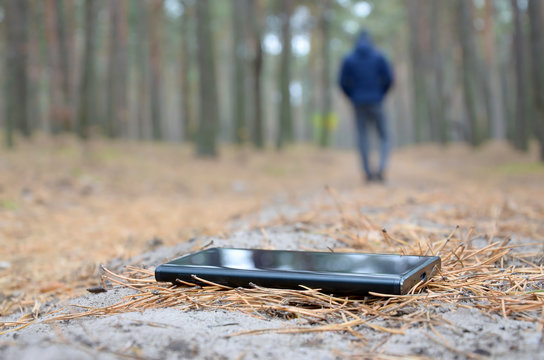 Young man loses his smartphone on Russian autumn fir wood path. Carelessness and losing expensive mobile device concept