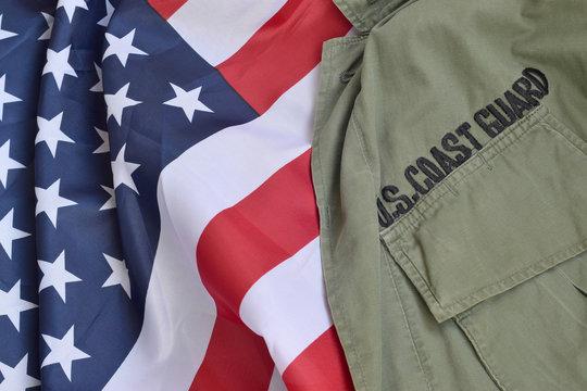 Old US Coast Guard uniform lies on folded United States Flag