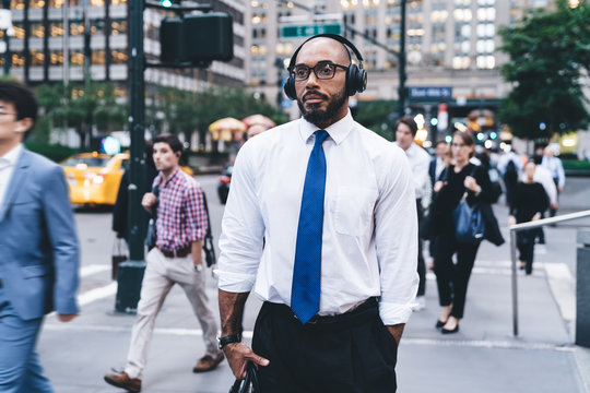 Thoughtful elegant male using wireless headphones on street