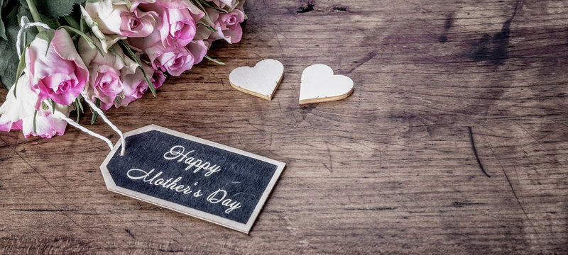 Happy Mother's Day background vintage - Bouquet of pink roses on rustic wooden table and two wooden hearts, with space for text