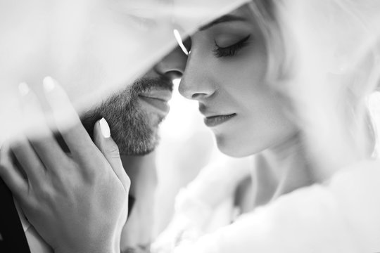 Black and white foto of amazing smiling wedding couple. Pretty bride and stylish groom posing  and kisses tenderly in the shadow of a flying veil. Romantic moment.Together. Wedding. Marriage.