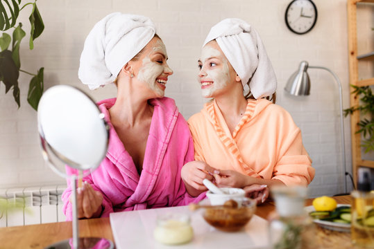 Mother and daughter in bathrobes and towels on head using natural cosmetics and having fun together at home
