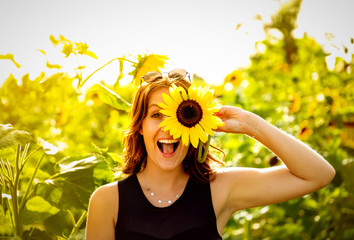 Fotorollo Gelb Young woman laughs with a sunflower on her face