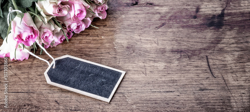 Bouquet of pink roses on rustic wooden table and two wooden hearts, with space for text