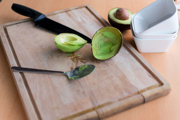 ausgelöffelte Avocado neben ihrer Schale auf einem Holzbrett