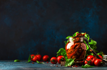 Italian Sun Dried tomatoes in olive oil with green basil and spices in glass jar on blue kitchen table, copy space Fototapete