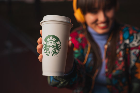 New York, USA - January 10, 2020: Blurred Cheerful smiling woman listening to music with yellow headphones and holding a cup Starbucks coffee