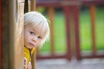 Blonde little toddler child in yellow jacket, playing on the playground