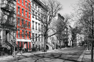 Red brick building highlighted on a block of old black and white buildings in the East Village of New York City