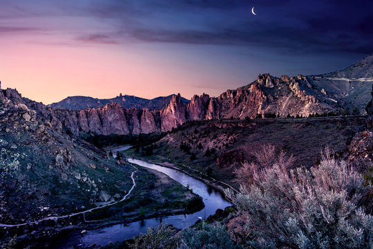 Smith Rock State Park landscape of mountains and a river under a violet evening sky in Bend, Oregon USA.