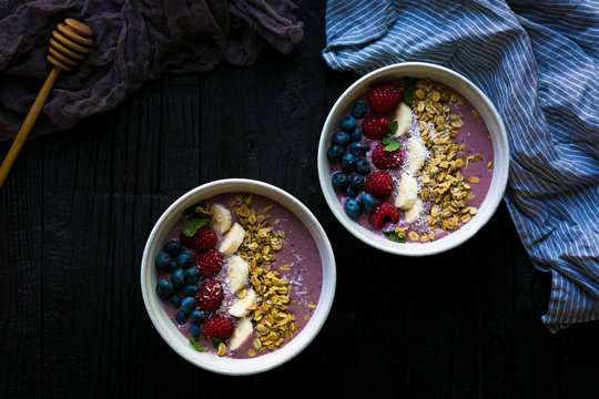 Two acai berry smoothie bowls shot from overhead.