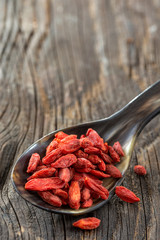 Wolfberry Other names are Goji, goji berry isolated on spoon on wooden background
