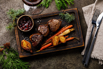 Grilled Venison Steak with baked vegetables and berry sauce and Red wine on dark background