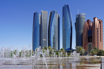 view of a row of scyscraper in abu dhabi behind a fountaion, beautiful blue sky and green trees, with some reflections in the water, skyline