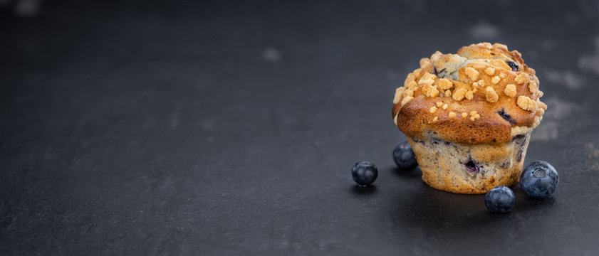 Fresh made Blueberry Muffins on a slate slab (close-up shot; selective focus)