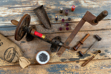 Antique tools for reloading of hunting cartridges, powder measure, cartridge wad tampers, a lot of small bags with lead shots on a wooden background