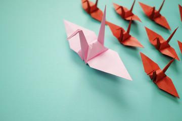 ピンクの大きい折り鶴が複数の茶色で小さい折り鶴を率いている。左に青緑のスペースがある。