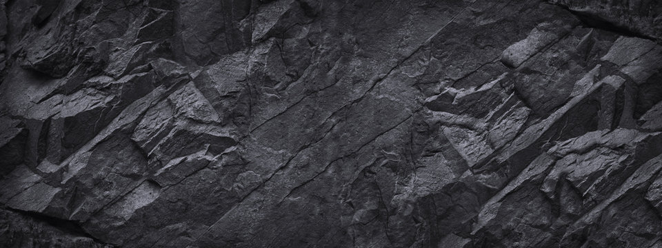 Black stone background. Dark gray grunge banner. Black and white background. Mountain texture. Close-up. Volumetric. The rocky backdrop. Abstract black rock background. Detail.