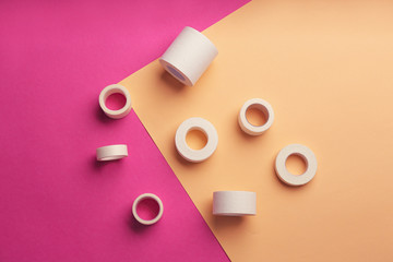 Sticking plaster rolls on color background, flat lay