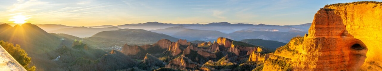Panoramic shot of mountains and cliffs with the sun shining in the background in Las Médulas, Spain