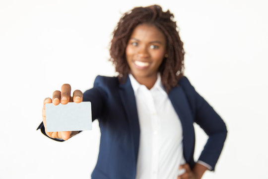 Happy businesswoman showing blank card. Cheerful young African American woman holding blank business card and smiling at camera, selective focus. Business concept