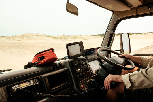 A man driving a tour truck on sand dunes in Australia