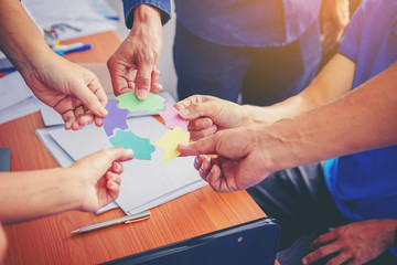 Business people putting connect round colorful jigsaw puzzle. Team work and strategic solution concept.
