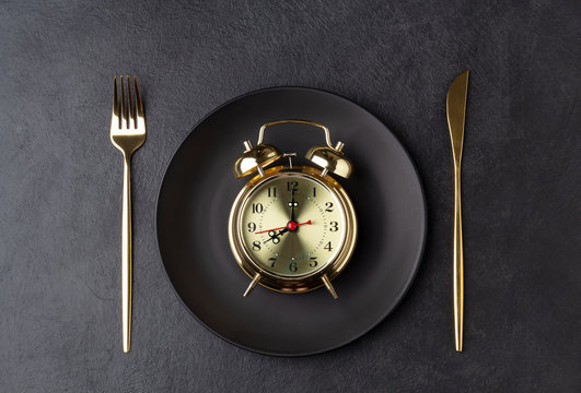 Golden alarm clock on a black plate with a golden knife and fork