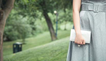 Woman in shining silver dress holding wallet in outdoors.