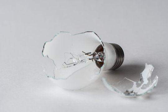 Broken light bulb isolated on white background with shattered piece of lightbulb