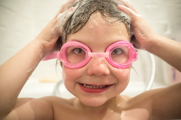 Little boy protects his eyes from shampoo foam with goggles