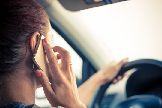 Close-up of woman talking on the phone while driving car.