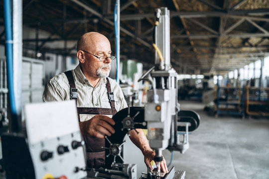 Senior man with bald head, working at factory for special machine