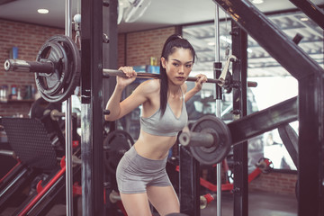 Poster Fitness sporty woman does the exercises with bar. photo of muscular woman in sportswear. fitness women exercising are lifting bar at vintage fitness gym. concept strength and motivation.