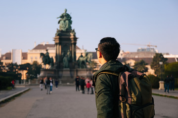 Back view portrait of Asian male tourist backpacker carrying a bag in Maria Theresa Monument in Vienna, Austria, Europe Fotomurales