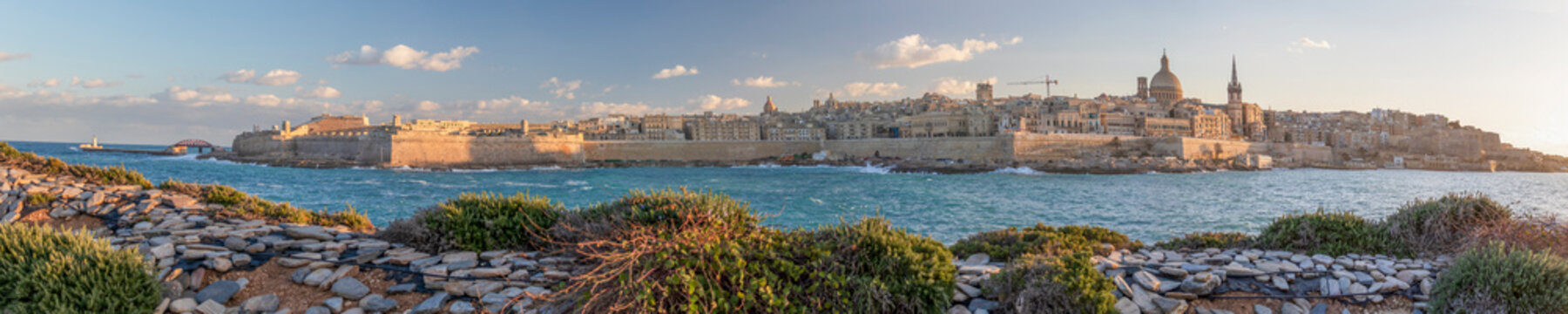 Panoramic view of Valletta, seafront skyline of the capital city of Malta from Sliema shoreline with green flora