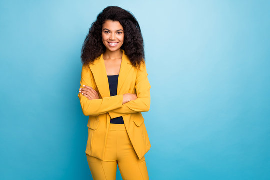 Photo of beautiful dark skin business lady holding hands crossed self-confident bossy person worker wear stylish yellow office costume isolated blue color background