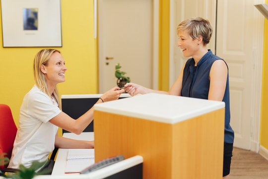 Female patient making payment at a dental surgery