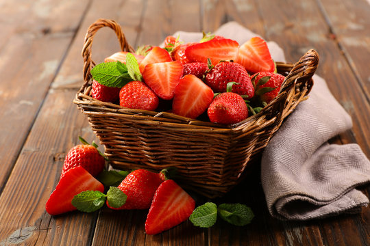 wicker basket with juicy strawberry on wood background