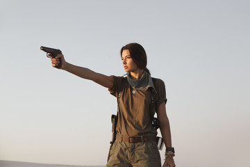Woman Standing With a Gun Outdoors in Desert