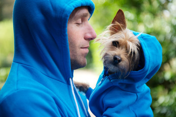 Man holding his best friend dog in matching blue hoodies outdoors in bright green park background