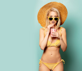 Beautiful blonde woman in bikini with paper cup